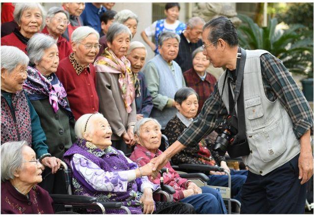 86岁的老年摄影爱好者谢金声为湖州社区里老年公寓的老人拍合影