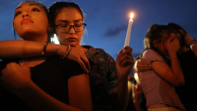 People attend a candlelight vigil at a makeshift memorial for victims of a mass shooting which left at least 22 people dead, on August 7, 2019 in El Paso, Texas