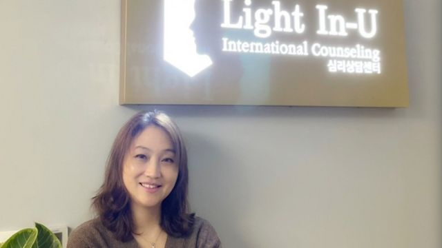 Julia stands next to a sign for her counselling centre, Light In-U.