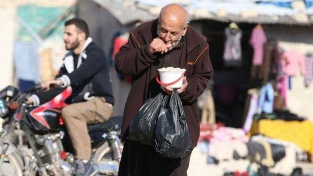 عجوز في حلب يمسك بحصته من المواد الغذائية الشحيحة في المدينة