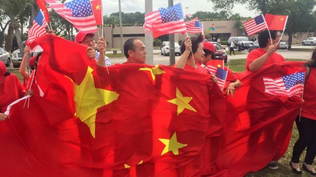 A group of China supporters wave Chinese and US flags as they wait for the arrival of Chinese President Xi Jinping at Palm Beach international airport on April 06 2017