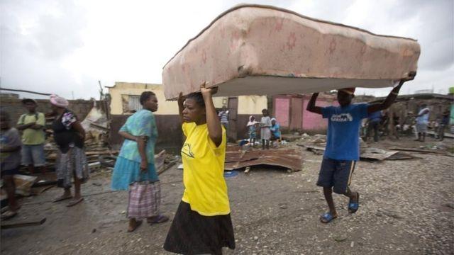 Residentes de Les Cayes trasladan un colchón a un refugio.