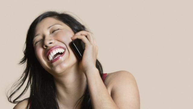 Mujer sonriendo y sosteniendo el celular