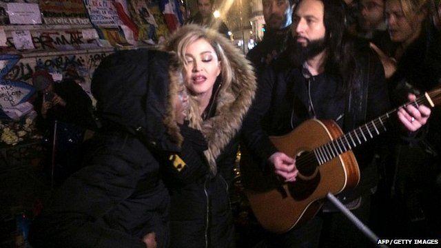 Madonna (C) sings next to her guitarist Monte Pittman (C-R) and her adoptive son David Banda