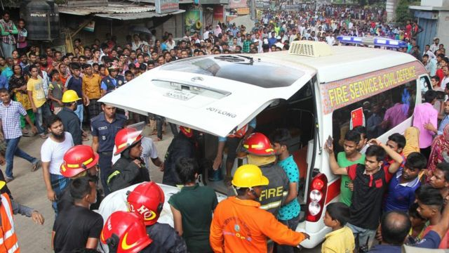 Firefighters carry victims to an ambulance after factory fire in Tongi, Bangladesh, on 10 September 2016