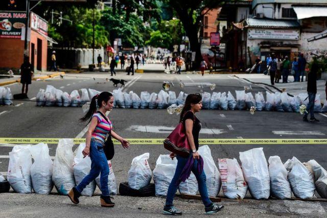 Dos mujeres pasan frente una calle cortada en el barrio de Petare, en la capital de Venezuela, Caracas, el 26 de julio.