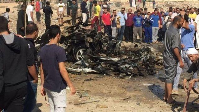أشخاص يحيطون بسيارة انفجرت