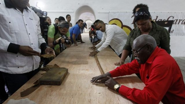 """Jose Castelar Cairo, known as """"Cueto"""" (R), presents to the public the world""""s longest cigar in Havana, Cuba, 12 August 2016."""