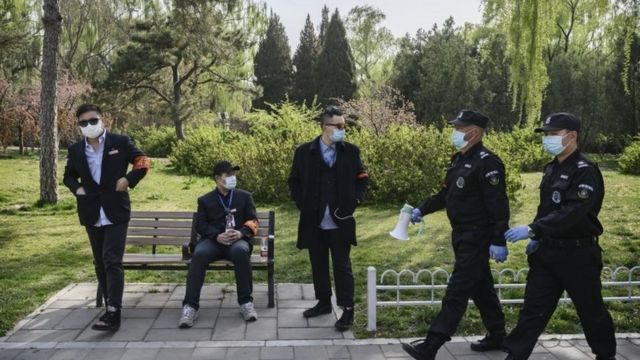 Chinese security guards and park workers on 5 April at a park in Beijing