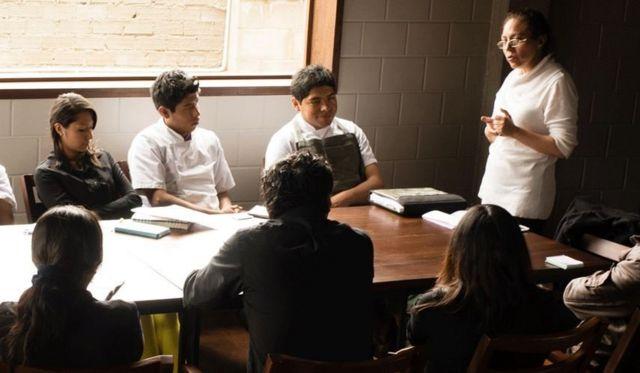 Mujer enseña a unos jóvenes sentados en una mesa.