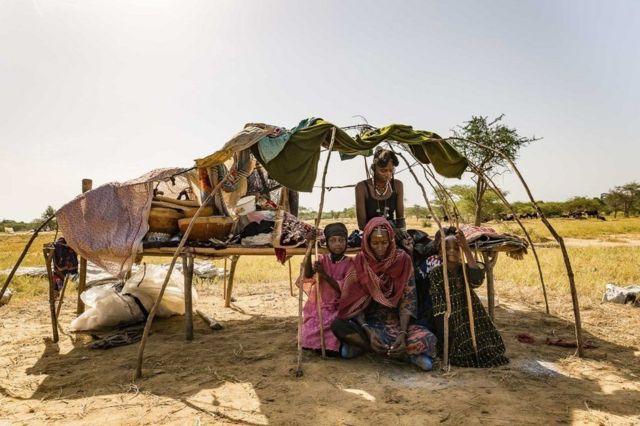 सूर्य की गरमी से बचने की कोशिश करता एक परिवार