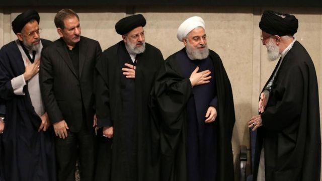 Raisi, no centro e o presidente Hassan Rouhani (segundo à esquerda) cumprimentam o aiatolá Ali Khamenei em um memorial em 2020