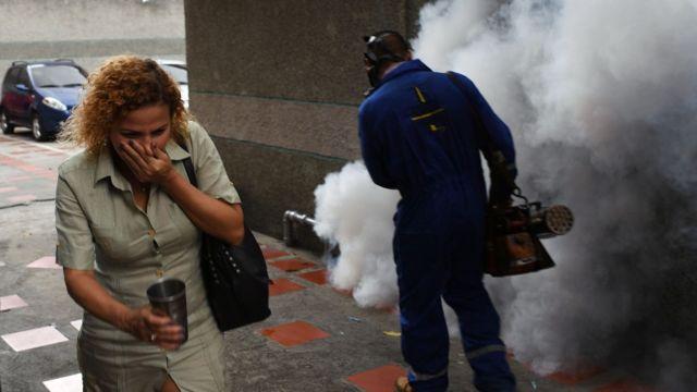 Un mujer se cubre la boca a pasar junto a un trabajador municipal que está rociando productos químicos para contener la propagación de mosquitos en Venezuela