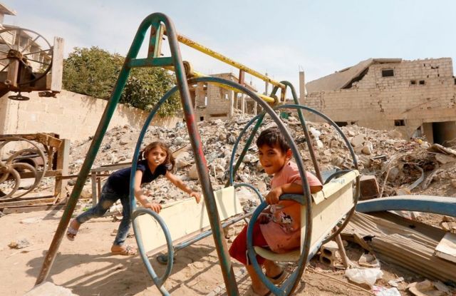 Syrian children play amidst badly damaged buildings in Zabdin, in the eastern Ghouta region on the outskirts of Damascus, on October 08, 2018