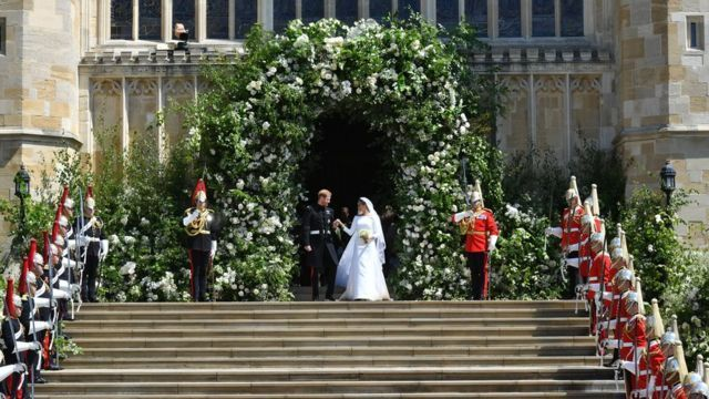 Prince Harry and Meghan Markle leave St George's Chapel though a gateway of flowers