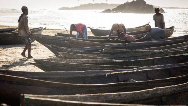 Mendaratkan pirogue ke pantai saat matahari terbit.