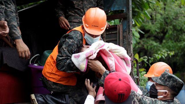 Miembros del ejército suben un bebé a un camión en Honduras