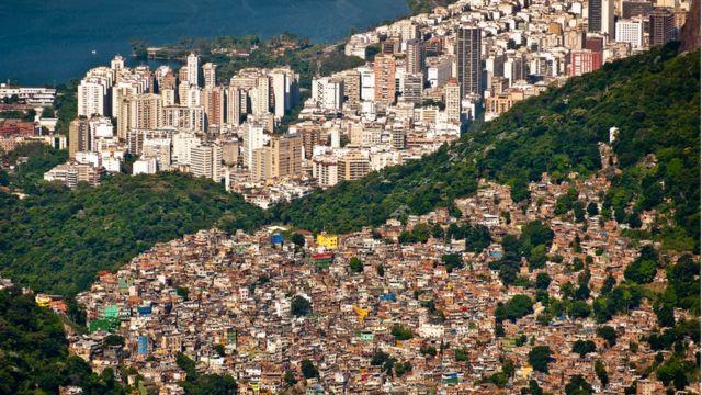 Vista do Rio de Janeiro com favela da Rocinha em primeiro plano e bairro de classe média ao fundo