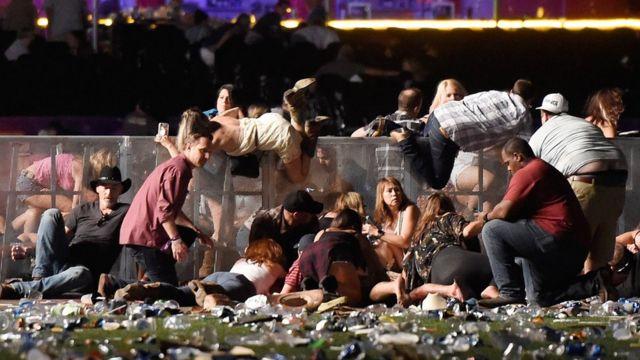 Gente saltando las barreras para refugiarse durante el tiroteo