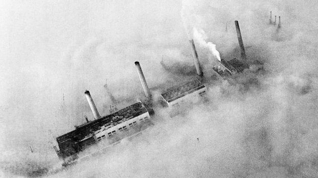As chaminés de uma fábrica do East End atravessam o manto de poluição que cobre Londres. Circa 1952