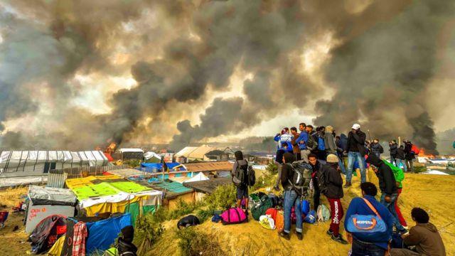 مهاجرون يتطلعون الى النيران وهي تلتهم مخيم الغابة في كاليه