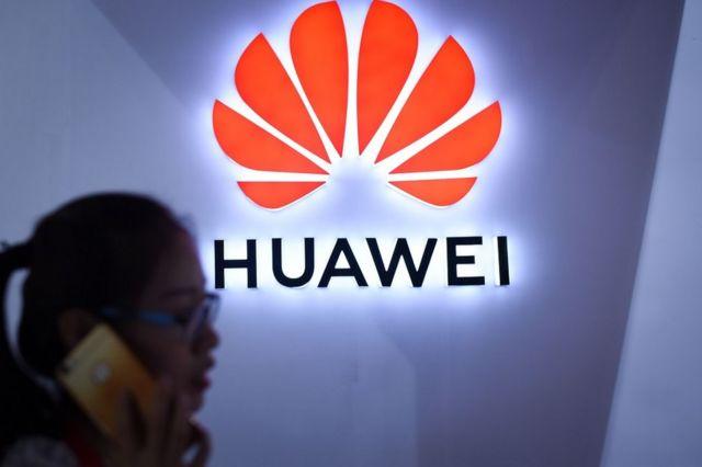 Pessoa fala ao telefone em frente a logo da Huawei