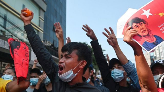 People show the three-finger salute as they rally in a protest against the military coup, 8 February