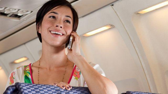 Una mujer habla por teléfono dentro de un avión.
