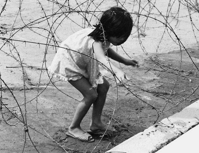 Una niña juega en un alambre de púas, en Vietnam.