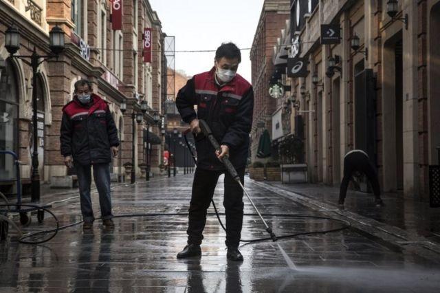 Trabajadores limpian una calle de Wuhan