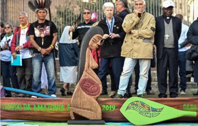 Una escultura de madera tallada de una mujer embarazada y un modelo de piragua