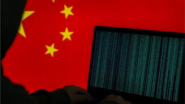 Imagen de stock de una persona encapuchada que trabaja en la computadora frente a una bandera china.