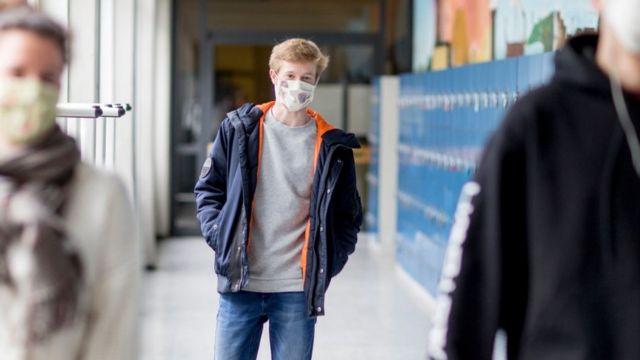 Un joven con mascarilla en una escuela