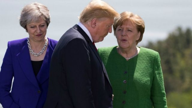 Theresa May and German Chancellor Angela Merkel look on as US President Donald Trump arrives for the family photo at the G7 Summit June 8, 2018