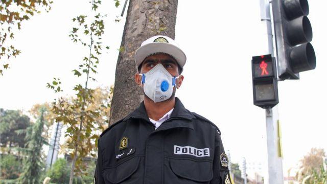 شرطي يرتدي كمامة في أحد شوارع طهران