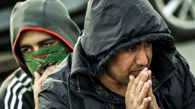"""مهاجران يجلسان قرب مخيم """"الغابة"""" في كاليه"""