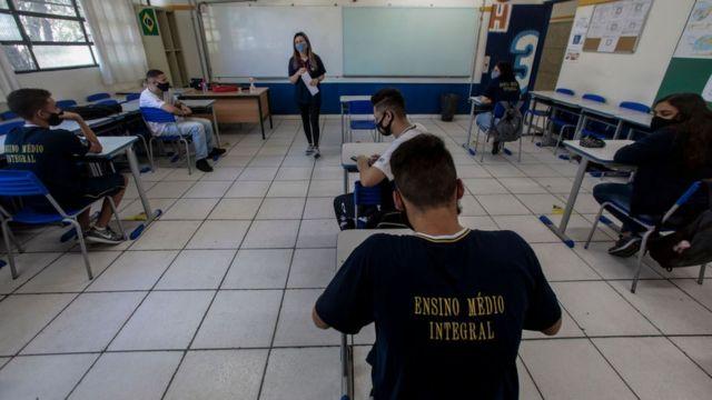 Professora em sala de aula e alunos sentados e distantes entre si. Todos estão com máscaras.