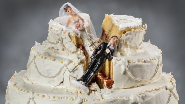 Collapsed bride and groom figures on a wedding cake