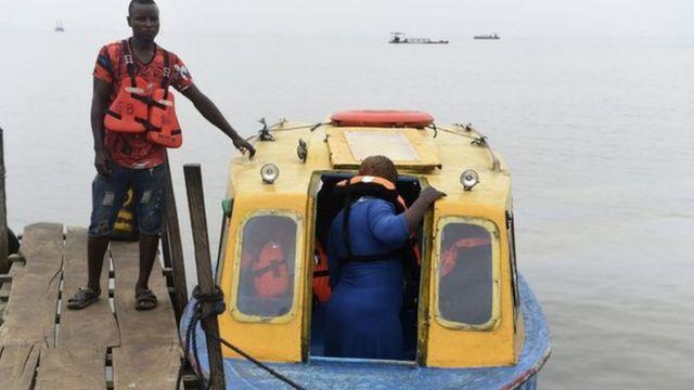 Fery operator stand dey wedge di ferry as passenger dey enta inside.