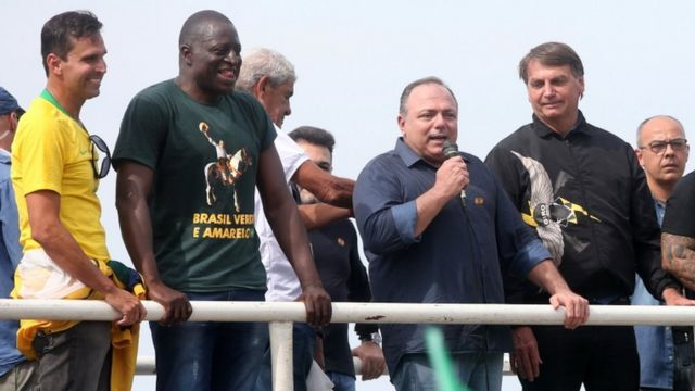 Pazuello fala no microfone em cima de carro de som, ao lado de Bolsonaro e outros homens, todos sem máscara