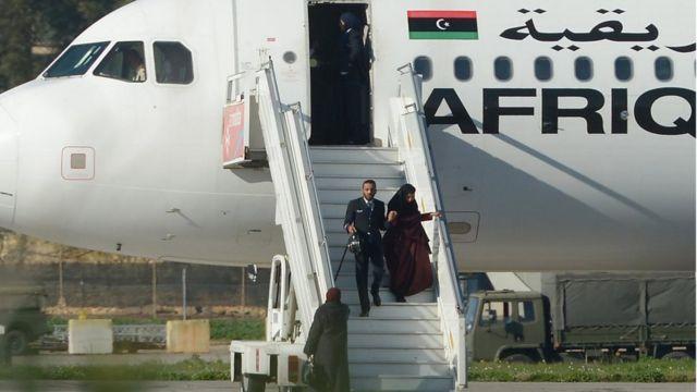 أحد أفراد طاقم الطائرة المختطفة وهو يساعد إحدى الراكبات لدى نزولها في مطار مالطا الدولي