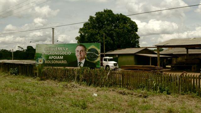 Outdoor com foto de Jair Bolsonaro dentro de serraria em Ariquemes (RO).