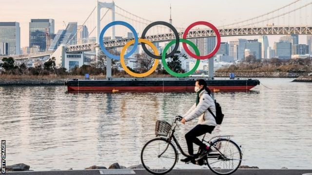 A woman wearing a facemask as a preventive measure against the spread of covid-19 rides past the Olympic logo