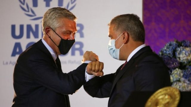 """The United Nations High Commissioner for Refugees (UNHCR) Filippo Grandi bumps elbows with Colombia""""s President Ivan Duque during the announcement of the granting of legal status of temporary protection to Venezuelan migrants, in Bogota, Colombia February 8, 2021."""