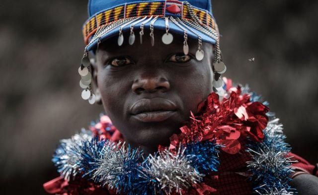 مراهق من كينيا ينتمي إلى إثنية شعب الماساي (هم مجموعة عرقية نيلية وهم شبه رحل يتمركزون في كينيا وشمال تنزانيا) يخرج من الغابة الأربعاء عقب حفل ختانه للاحتفاء بانتقاله إلى مرحلة البلوغ.