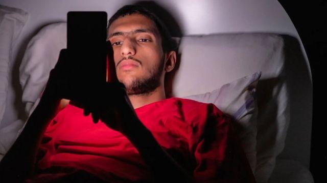 joven con un celular en la cama.