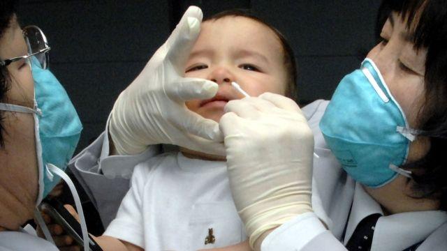 ممرضتان تقومان بتطعيم طفل في كوريا الجنوبية