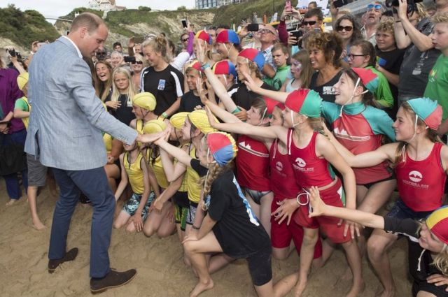 Prince William, Duke of Cambridge greets children as he visits the work of the Wave Project on Newquay's Towan Beach