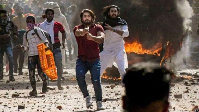 दिल्ली में सोमवार को हुई हिंसा में लाल शर्ट पहना एक व्यक्ति पिस्तौल के साथ नज़र आया