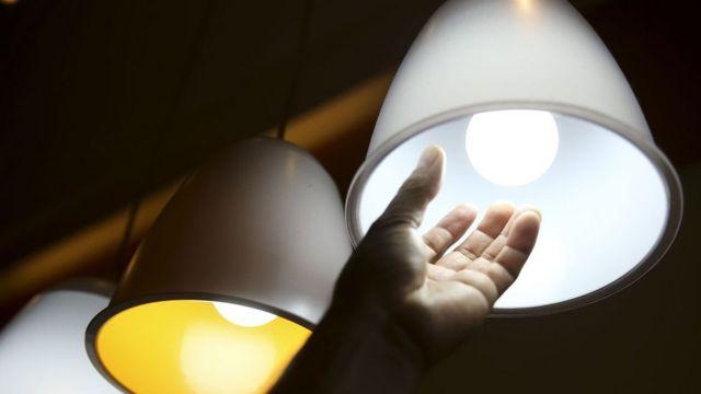Mão trocando lâmpada
